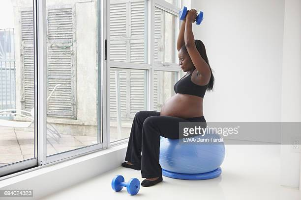 Pregnant Black woman sitting on fitness ball lifting weights