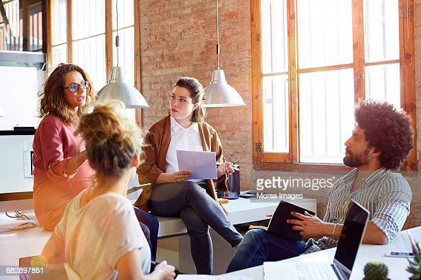 pregnant businesswoman discussing with colleagues - leanincollection stock pictures, royalty-free photos & images