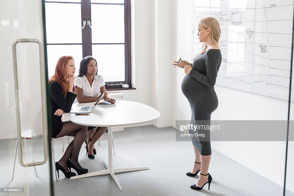 Pregnant businesswoman explaining to female colleagues in business meeting : Stock Photo