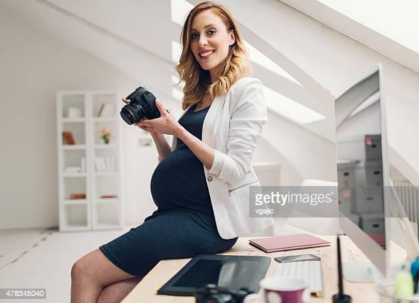 妊娠を持つビジネスウーマンデジタルカメラ、仕事で自分のオフィスにお問い合わせください。