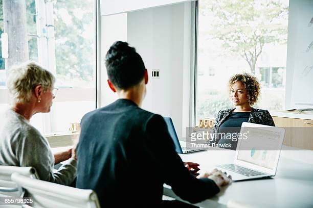 Pregnant businesswoman leading team meeting