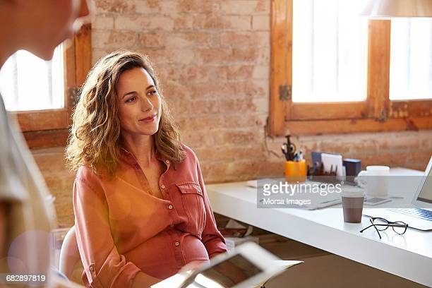 pregnant businesswoman looking away at desk - oranje stockfoto's en -beelden