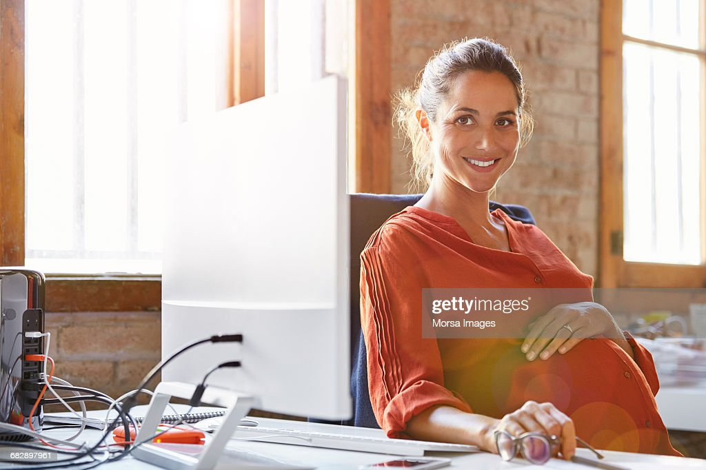 Pregnant businesswoman sitting at computer desk : Stock Photo