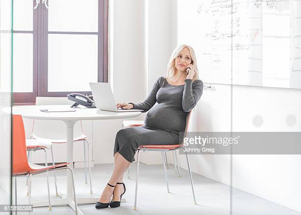 Pregnant businesswoman sitting on chair making phone call with laptop