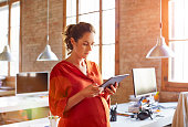 Pregnant businesswoman using tablet PC in office