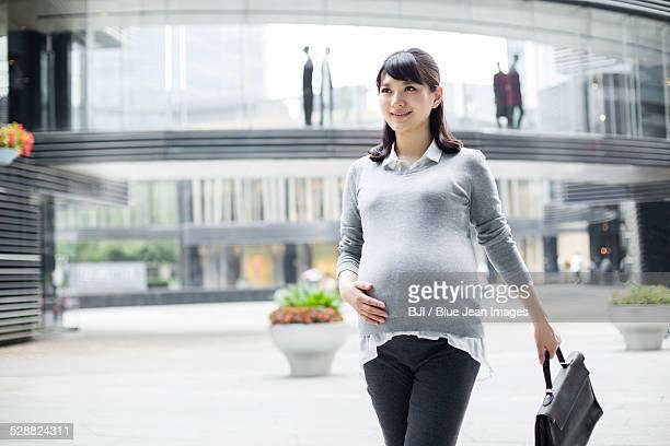 Pregnant businesswoman walking in city center