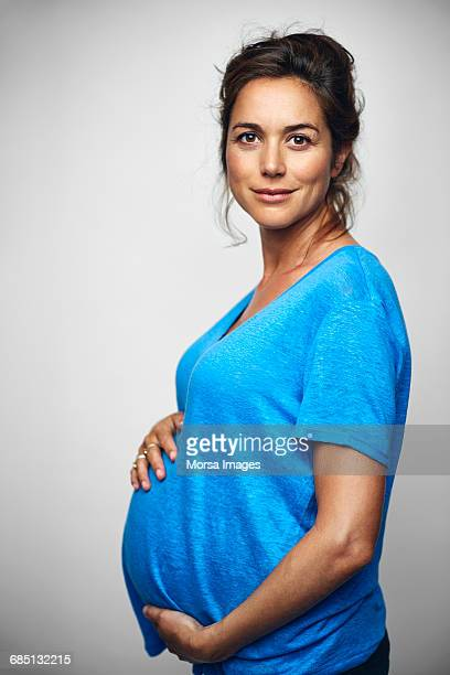 Pregnant businesswoman with hands on stomach