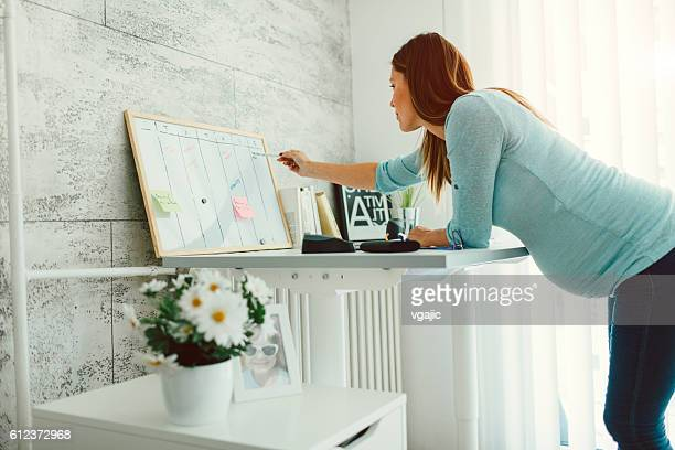 Pregnant Businesswoman Working In Her Home Office.