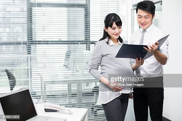 Pregnant businesswoman working with colleague