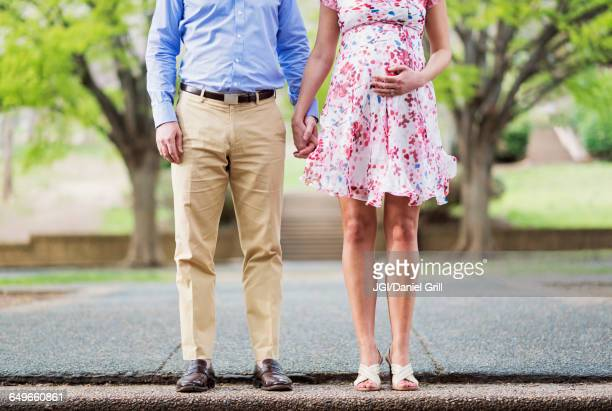 pregnant caucasian couple holding hands outdoors - khaki trousers stock pictures, royalty-free photos & images