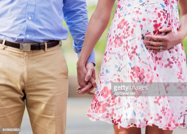 Pregnant Caucasian couple holding hands outdoors