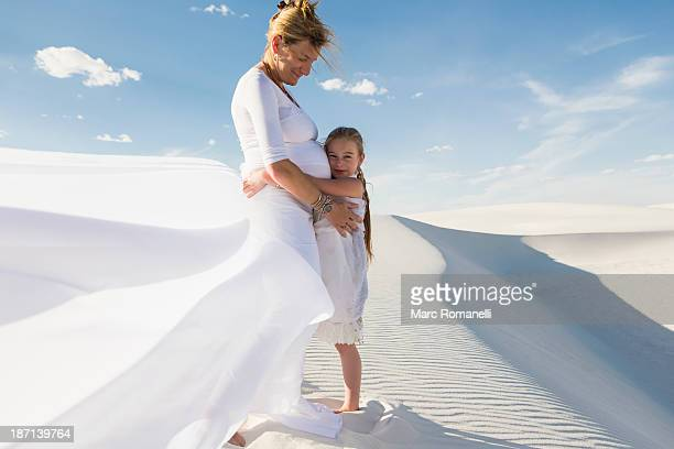 Pregnant Caucasian mother and daughter hugging in desert