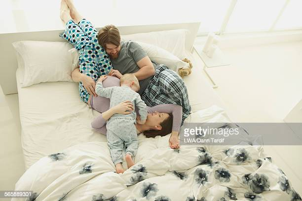 Pregnant Caucasian mother, father and son playing on bed