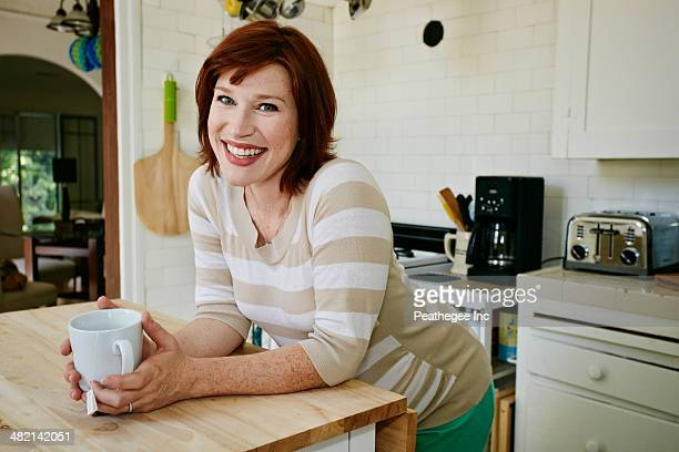 Pregnant Caucasian woman drinking cup of tea in kitchen