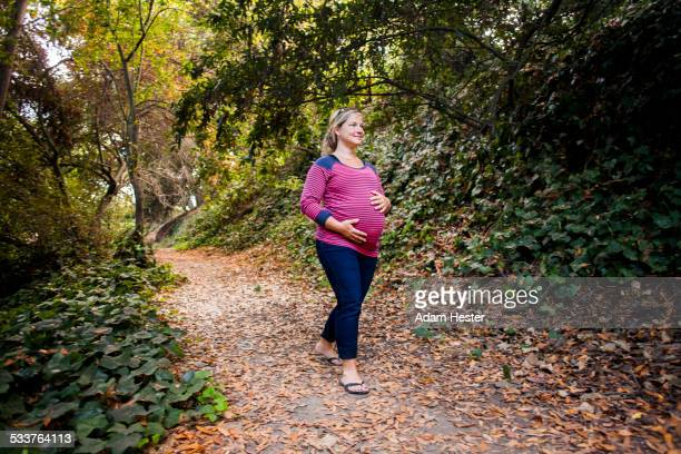 Pregnant Caucasian woman holding her stomach on forest path
