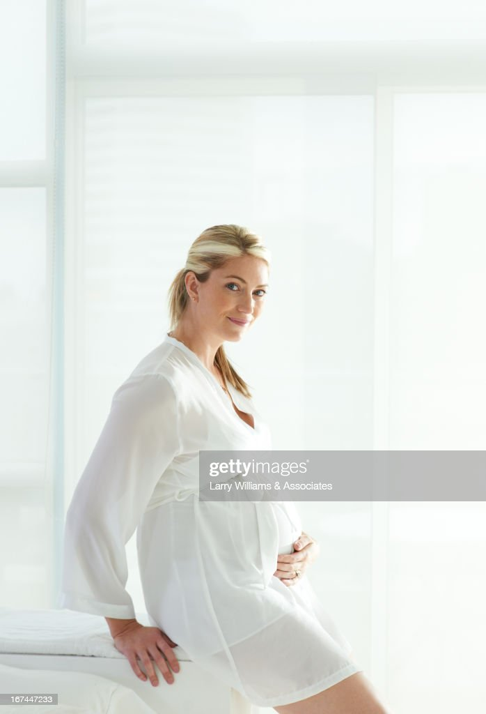 Pregnant Caucasian woman holding stomach : Stock Photo