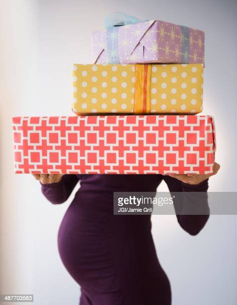 pregnant caucasian woman holding wrapped gifts - baby shower stock photos and pictures