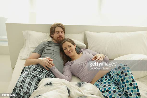 Pregnant Caucasian woman laying with husband on bed