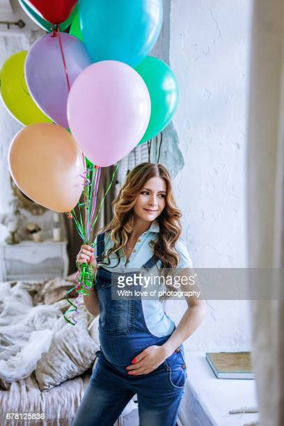 Pregnant caucasian woman with balloons in jeans