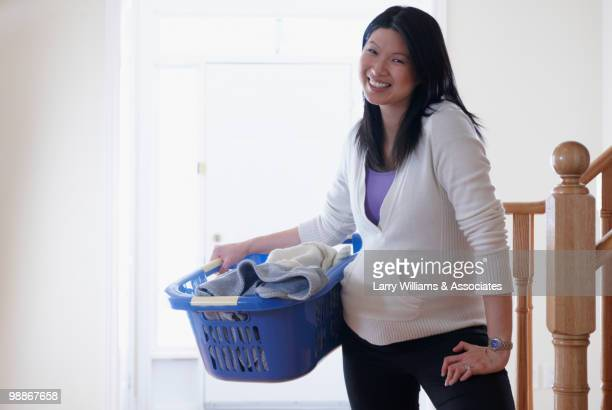 Pregnant Chinese woman holding laundry basket