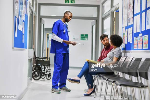 pregnant couple chatting to a doctor - sturti stock pictures, royalty-free photos & images