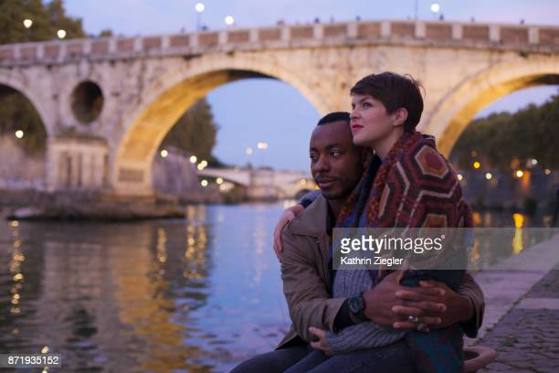 Pregnant couple embracing by Tiber River at the blue hour , Rome, Italy