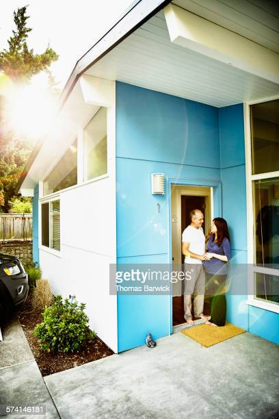 Pregnant couple embracing in doorway of home
