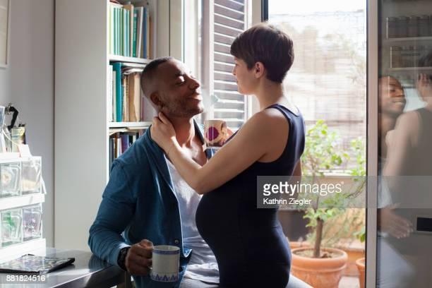 pregnant couple having tea together in kitchen - legame affettivo foto e immagini stock