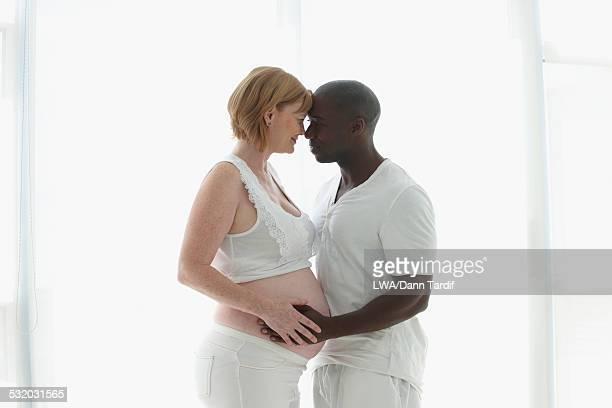 Pregnant couple hugging near window