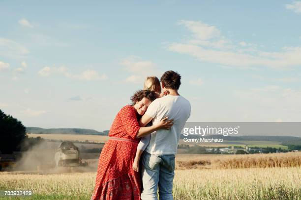 Pregnant couple in wheat field with toddler daughter watching combine harvester