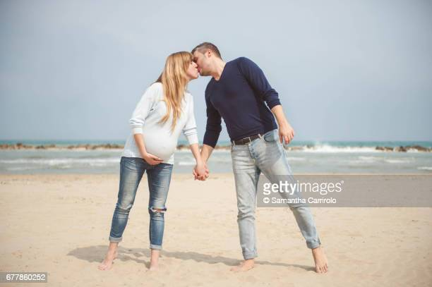 Pregnant couple kissing on the beach. Hand in hand. Casual clothes. Hand on the belly.