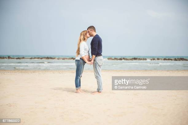 Pregnant couple kissing on the beach. Hand in hand. Casual clothes.