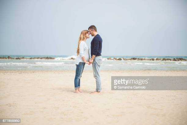 Pregnant couple on the beach. Hand in hand. Casual clothes.