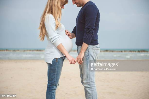 Pregnant couple on the beach. Hands on the belly. Casual clothes. Hand in hand.