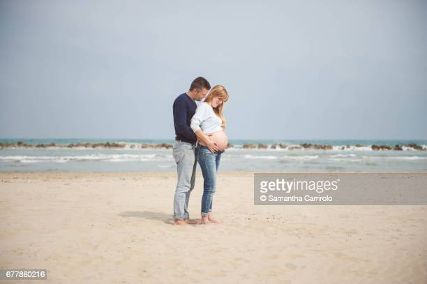 Pregnant couple on the beach. Hands on the belly. Embrace. Casual clothes.