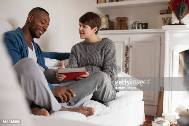 Pregnant couple on the sofa, looking at digital tablet