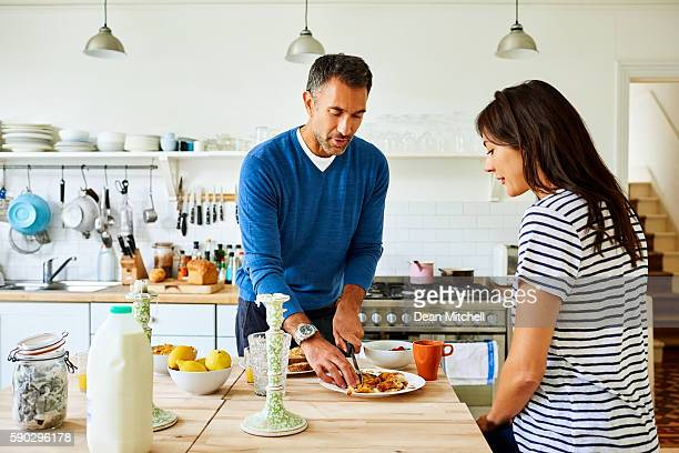 Pregnant couple preparing breakfast in kitchen