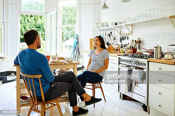 Pregnant couple sitting at breakfast table
