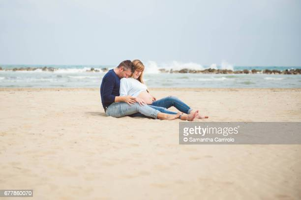 pregnant couple sitting on the beach. embrace. casual clothes. - abbracciare una persona stock pictures, royalty-free photos & images