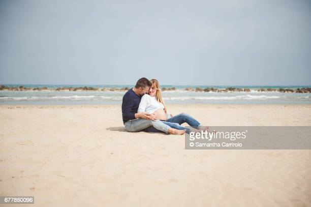 Pregnant couple sitting on the beach. Embrace. Casual clothes.