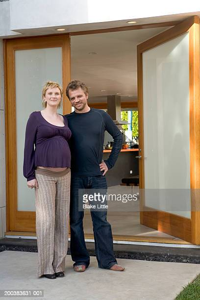 Pregnant couple standing outside house, portrait