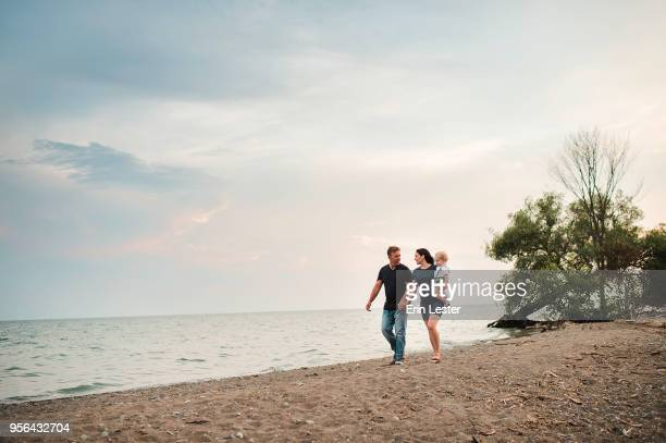pregnant couple strolling along beach with male toddler son, lake ontario, canada - ontario canada stock pictures, royalty-free photos & images