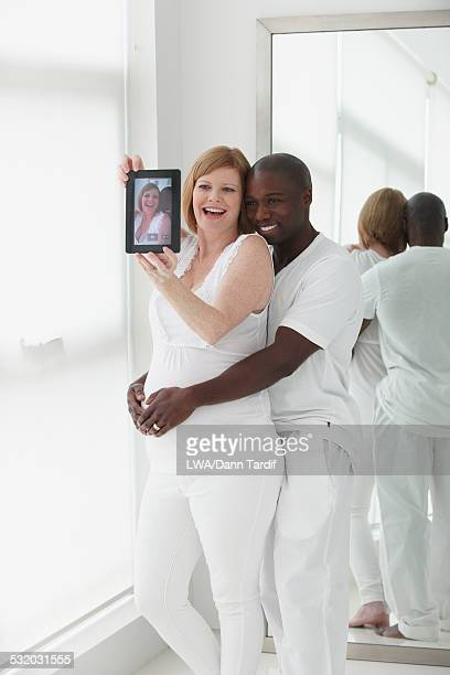 Pregnant couple taking selfie with digital tablet