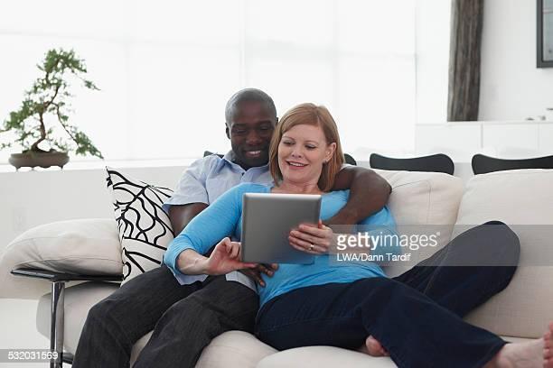 Pregnant couple using digital tablet on sofa