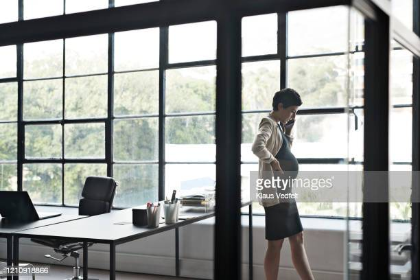pregnant entrepreneur talking over phone in office - cream coloured blazer stock pictures, royalty-free photos & images