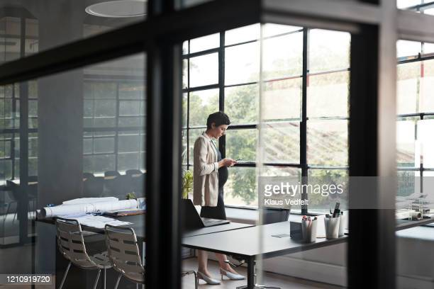 pregnant entrepreneur using phone in modern office - cream coloured blazer stock pictures, royalty-free photos & images