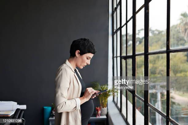 pregnant entrepreneur using phone in office - cream coloured blazer stock pictures, royalty-free photos & images