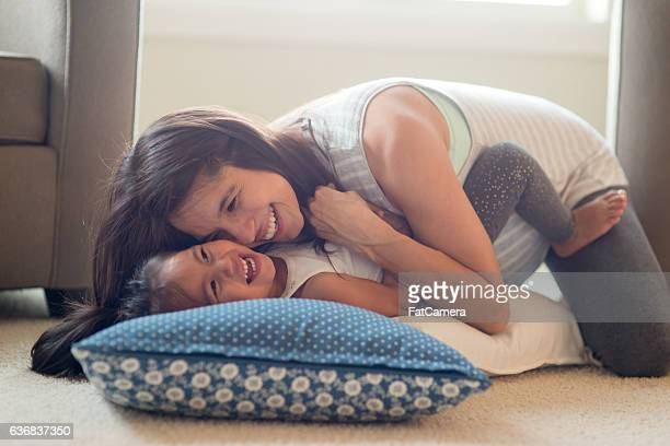 Pregnant ethnic mother playing and laughing with her toddler