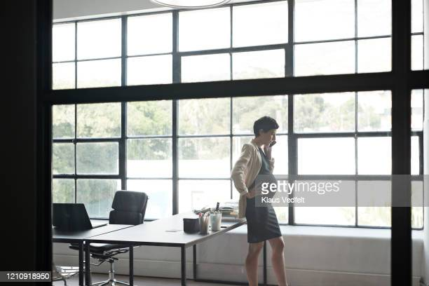 pregnant executive talking over phone in office - cream coloured blazer stock pictures, royalty-free photos & images