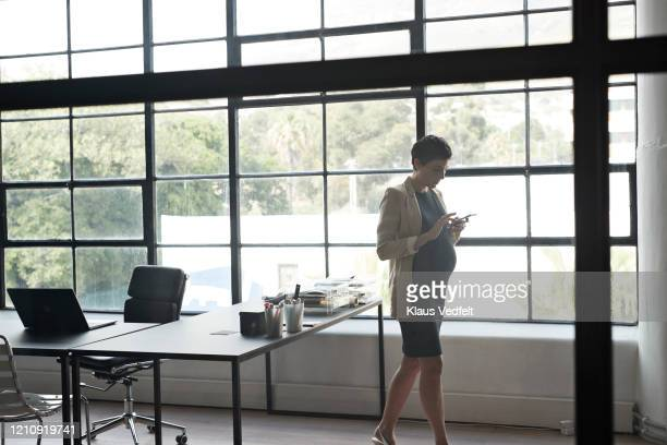 pregnant executive using phone in modern office - cream coloured blazer stock pictures, royalty-free photos & images
